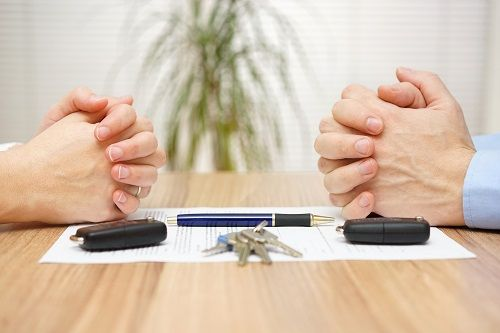 Two pairs of hands across a table, resting on a piece of paper with a pen, key fobs and keys.